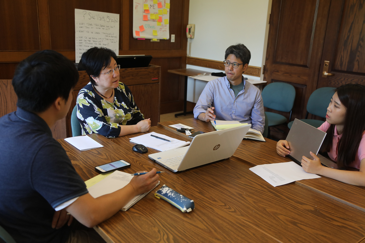 Four students seated around a professor at a conference table
