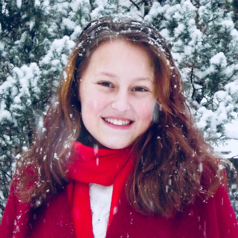 The smiling face of Olivia Thompson amid snow