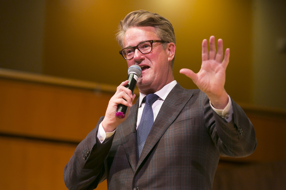 Joe Scarborough standing with a mic in hand