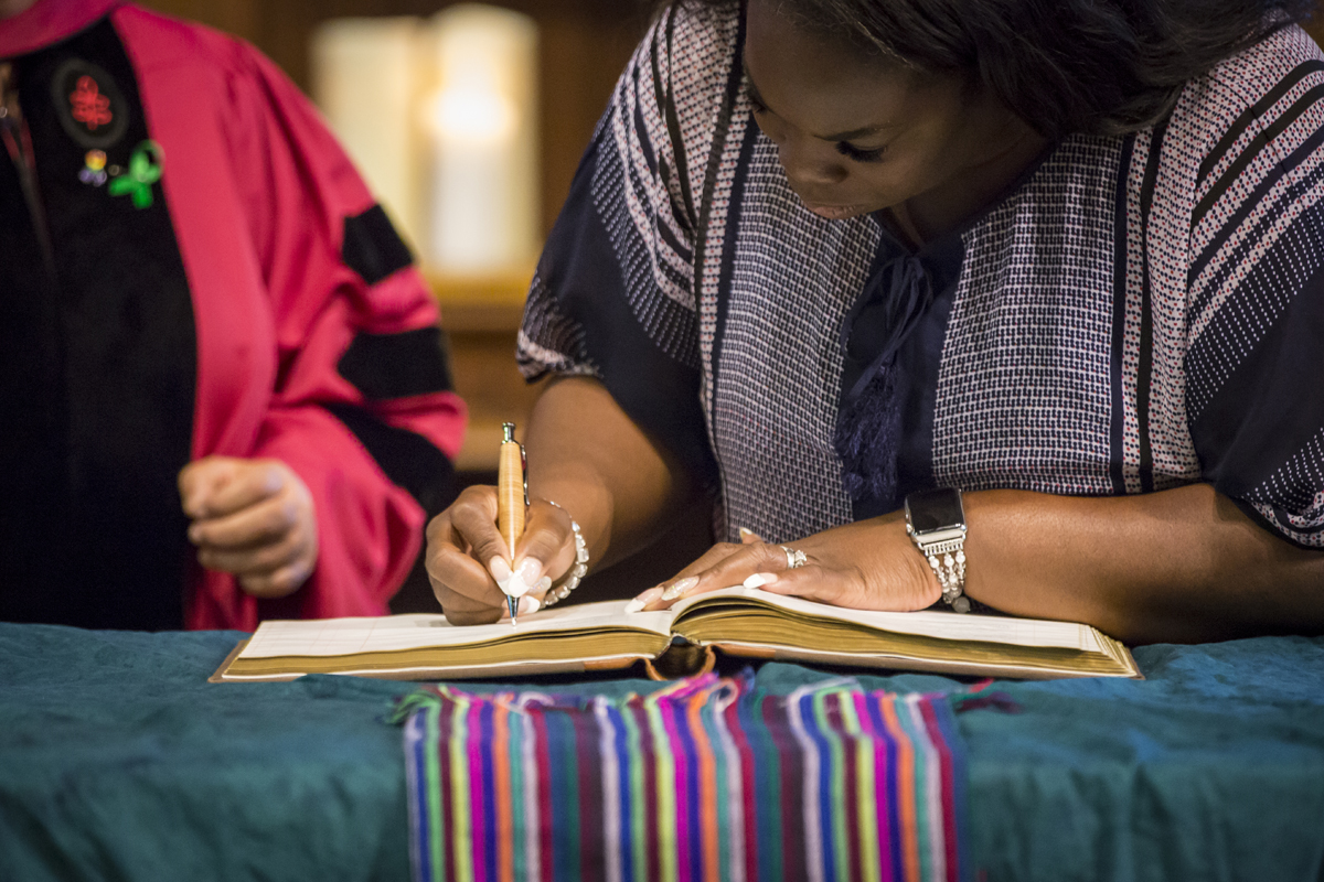 Incoming Theological School student signs book