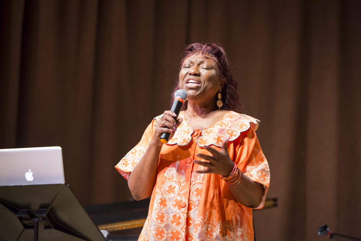 Cynthia Wilson singing into a microphone with her eyes closed