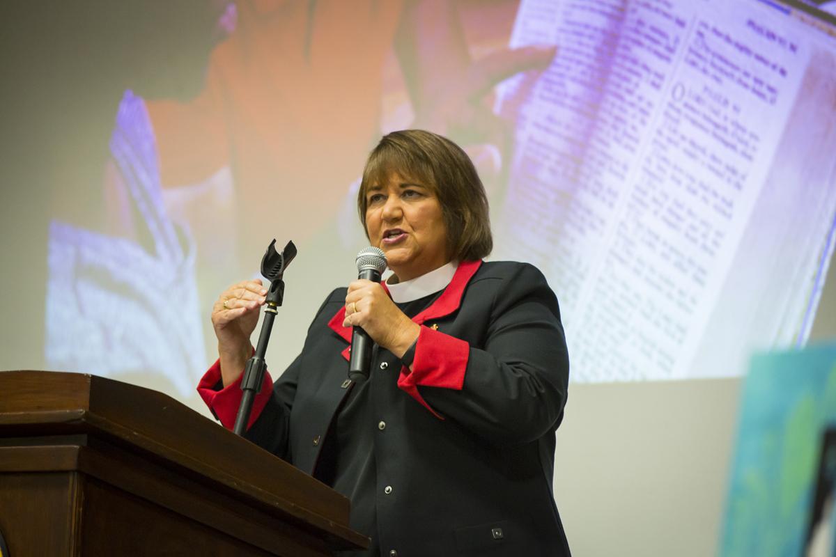 Bishop Karen Oliveto behind a lectern