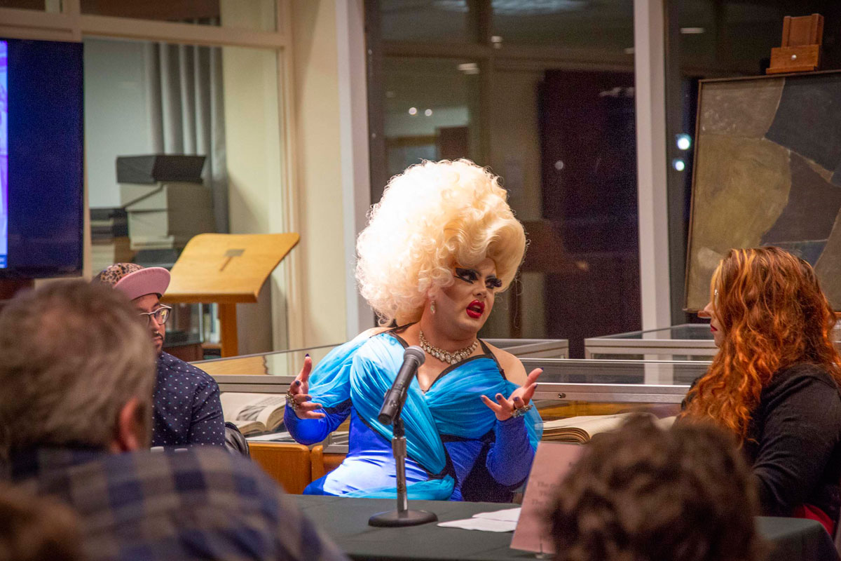 Drag artist Pissi Myles speaks while seated at a table