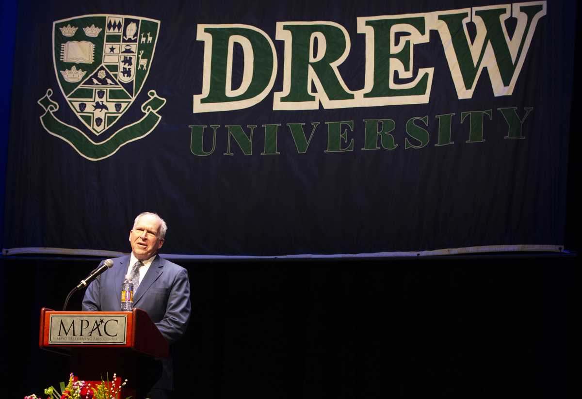 John Brennan standing behind a lectern with a Drew banner behind him