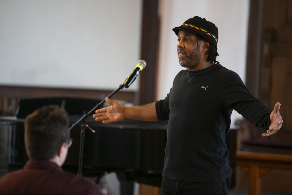 Victor Wooten standing with his arms outstretched
