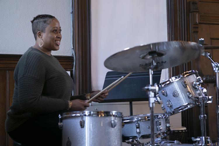 Student Tiffani Wheatley playing a drum set