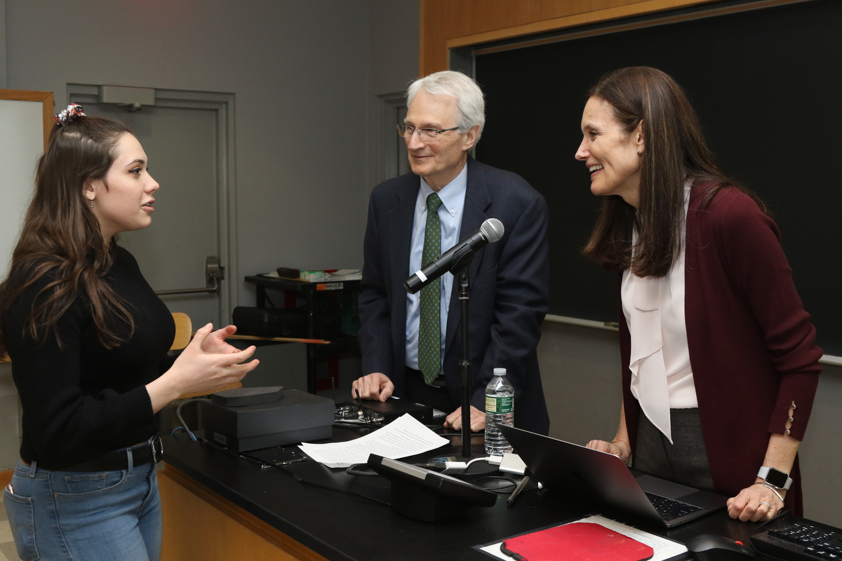 Student talks to scientist while RISE director looks on
