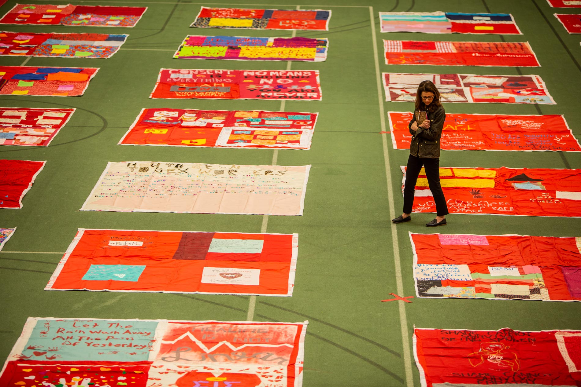 Woman standing amid red quilts on Simon Forum floor