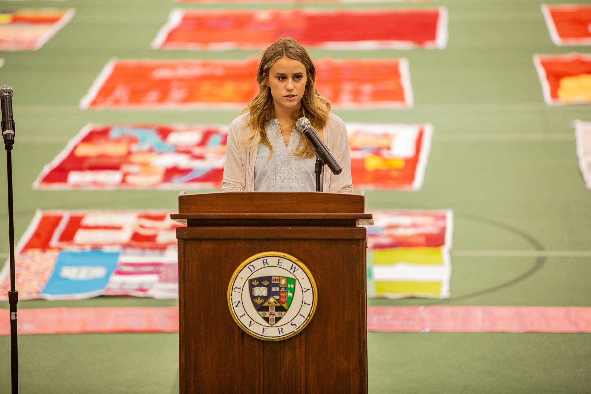 Samantha Savidge speaking behind a lectern