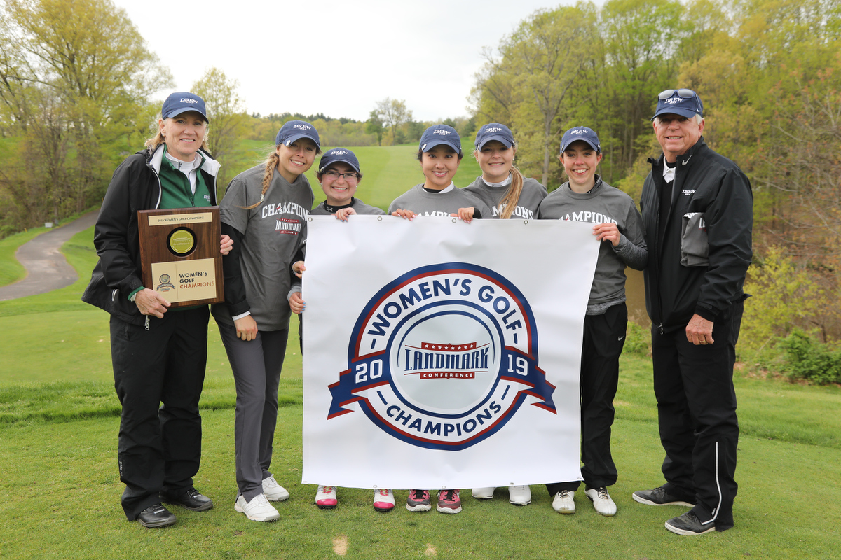 Women's golf team holding a championship banner on a course green