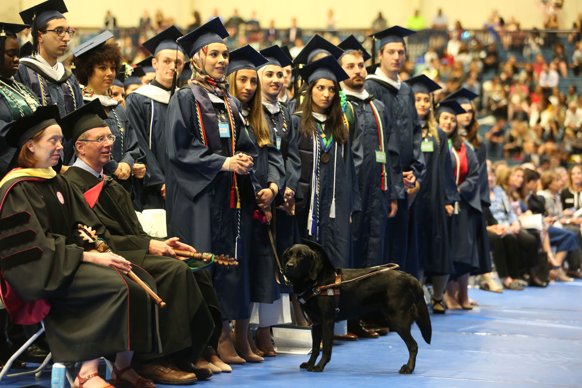 Line of Drew graduates in a row including a woman with a guide dog