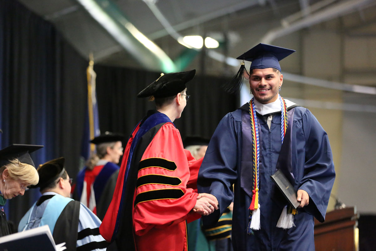 Male graduate shaking hands with Provost Debra Liebowitz
