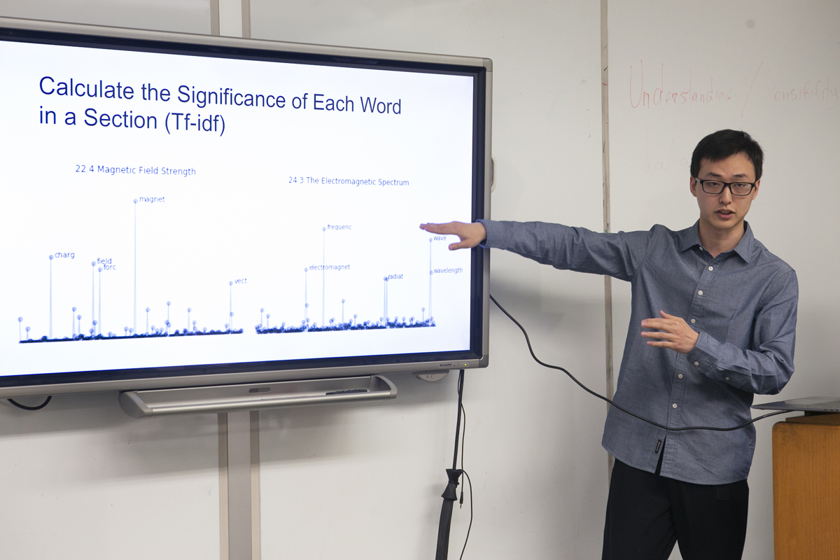 Peiyu Guo pointing to type on a projection screen