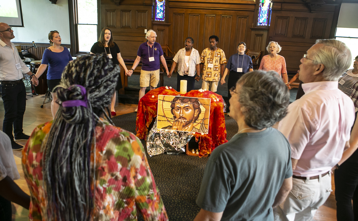Group stands in a circle holding hands inside Craig Chapel