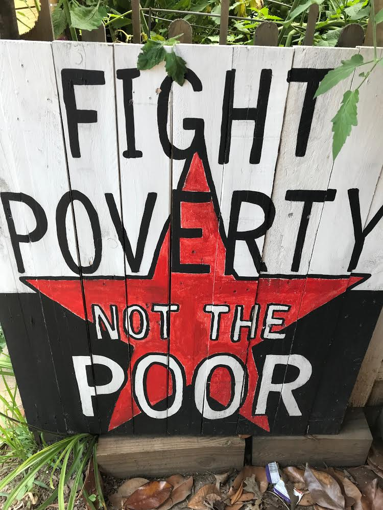 "Painted sign saying ""Fight poverty, not the poor."""